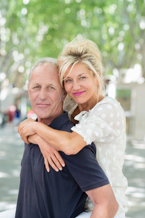 active couple: Middle-aged man giving an attractive smiling woman a piggy back ride as she hugs him around the shoulders on a hot summer day in town