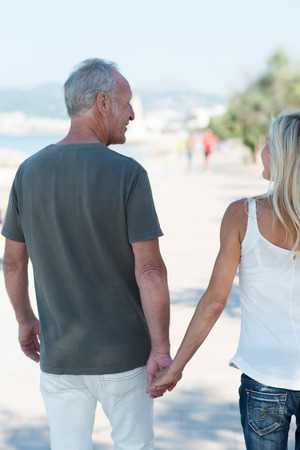 Mature man walking away from the cameras hand in hand with his wife along a seaside promenade photo