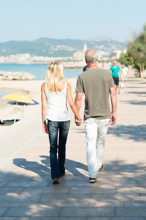 Middle-aged couple walking on a seafront promenade walking away from the camera hand in hand in the hot summer sunshine photo