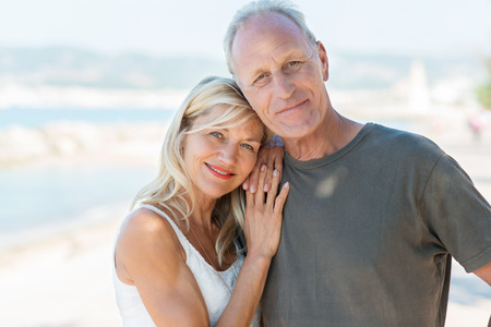 Portrait of an attractive loving middle-aged couple posing close together at the beach smiling at the camera photo