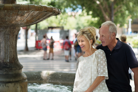 shady: Laughing mature standing couple alongside a fountain in a shady urban square watching the water cascading down
