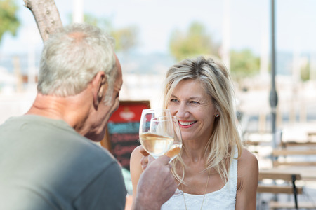 old bar: Happy mature couple toasting each other as they celebrate a summer vacation with white wine as they sit at an outdoor table at an open-air restaurant