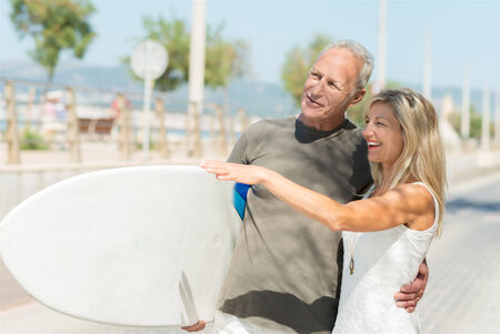 Mature man carrying a surfboard at the seaside with his arm around his attractive wife who is laughing and pointing something out to him photo