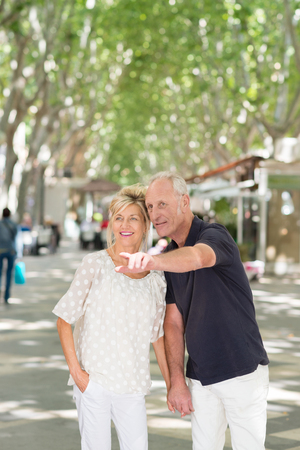 Attractive middle-aged man pointing out something to his wife as they stand close together peering into the distance in a tree lined urban street