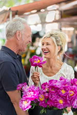 magenta flowers: Laughing vivacious middle-aged couple celebrating with a large bunch of colorful magenta flowers outdoors in an urban environment