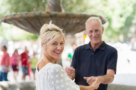 mature woman: Smiling beautiful tanned woman laughing as she turns to look at the camera while holding onto her husbands hands Stock Photo