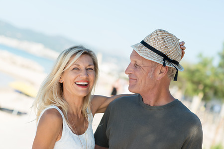 Laughing attractive middle-aged woman placing her trendy straw hat on her husbands head as they enjoy a day at the seaside Stock Photo