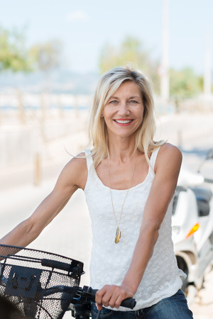 one senior woman only: Smiling attractive middle-aged woman in casual summer clothes holding a bicycle outdoors on a sunny street