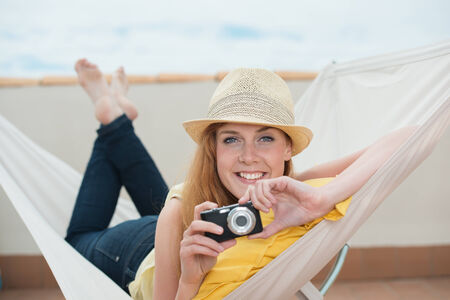 Smiling beautiful trendy young woman lying in a hammock on summer vacation holding a digital camera in her hand photo