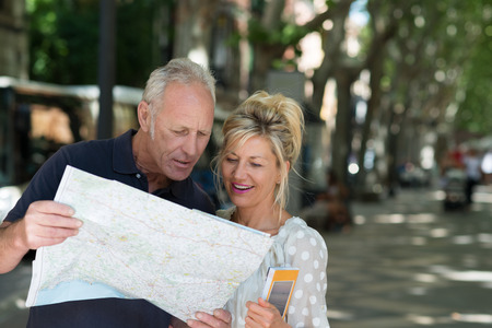 grownups: Middle-aged tourists consulting a map as they stand in a shady tree lined urban street looking for a specific travel destination Stock Photo