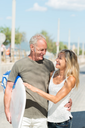 Happy fit tanned middle-aged couple going surfing walking along a sunny street arm in arm carrying a surfboard photo