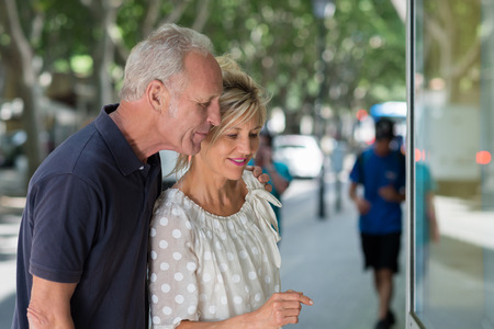 shopping trip: Middle-aged couple admiring shop merchandise through the store window as they stand close together on a tree lined urban street