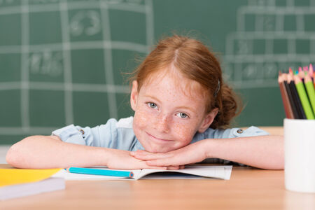 rueful: Tired little girl in class in school giving a rueful smile as she rests her head on her hands on the desk