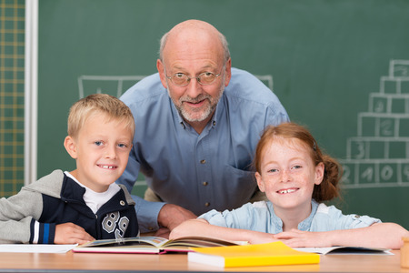 school teacher: Two happy young children with their elderly male teacher in the classroom posing together in front of the blackboard smiling at the camera