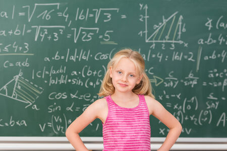 prodigy: Intelligent little girl child prodigy in class standing confidently in front of a blackboard covered in mathematical equations with her hands on her hips smiling at the camera