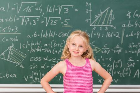 prodigy: Intelligent piccolo prodigio bambino in classe in piedi con fiducia davanti a una lavagna coperta di equazioni matematiche con le mani sui fianchi sorridendo alla telecamera Archivio Fotografico