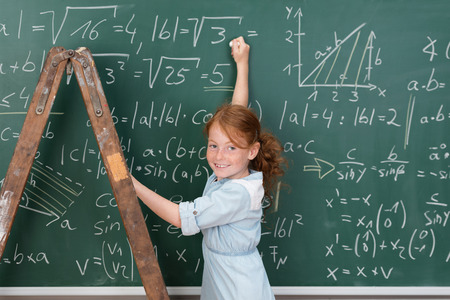 Young girl genius in maths class using a stepladder to reach the complex equations on the blackboard turning to grin at the camera photo