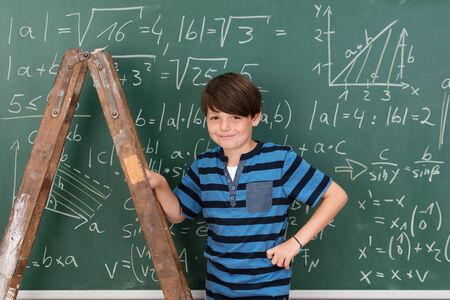 prodigy: Fiducioso sorridente giovane ragazzo prodigio a scuola durante le lezioni di matematica utilizzando una scala a pioli per raggiungere complesse equazioni alla lavagna Archivio Fotografico