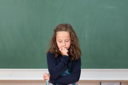 petite fille triste: Inquiet petite fille � l'�cole assis � son bureau en face du tableau noir vierge regardant d'un air morose vers ses notes de cours Banque d'images