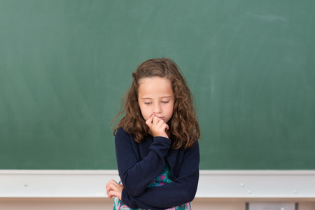 Worried little girl in school sitting at her desk in front of the blank blackboard staring morosely down at her class notes