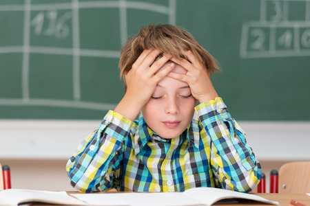 male headache: Young boy concentrating on his schoolwork sitting at his desk in the classroom with his head in his hands reading his class notes