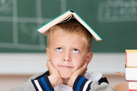 Little boy hoping to absorb knowledge sitting in class with his text book balanced on his head looking up with a rueful smile Stok Fotoğraf