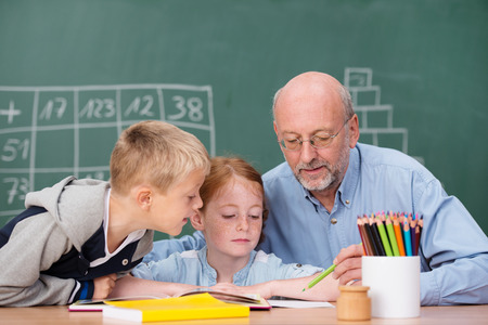 Young boy and girl in class with an elderly male teacher sitting at a desk together as he explains something in a book or class notes to them photo
