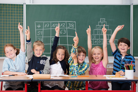 Enthusiastic group of young kids in class sitting in a row at their desk raising their hands in the air to show the know the answer to a question photo