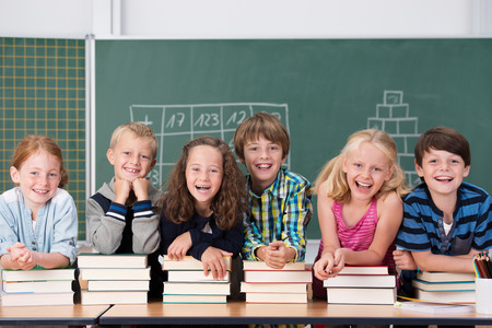 kids class: Laughing group of young school kids in class with young boys and girls leaning on piles of hard cover text books on a long table in front of a blackboard