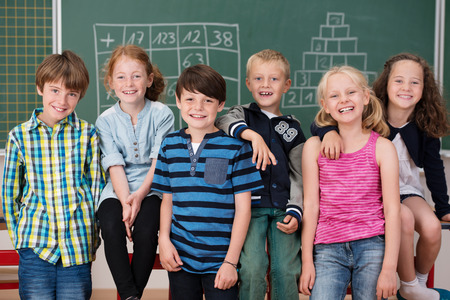 Portrait of young school children in class posing in a row together in front of the blackboard laughing at the camera