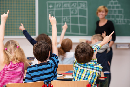 Intelligent group of young school children all raising their hands in the air to answer a question posed by the female teacher, view from behind Stockfoto