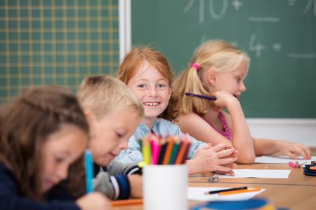 escuela primaria: Chica joven feliz en la escuela primaria sentado en una mesa compartida con sus compañeros de clase mirando a la cámara con una sonrisa descarada feliz