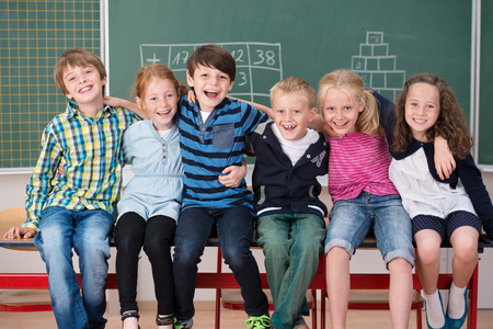 Laughing group of young friends in class sitting in a row in front of the chalkboard grinning happily at the camera