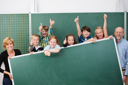 Cheering happy young school children standing holding a large blank blackboard with copyspace together with a smiling male and female teacher at either end photo