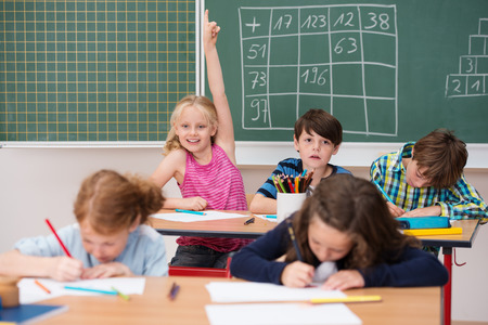 attract attention: Intelligent enthusiastic little girl in class holding up her hand with a happy smile to attract attention and answer a question Stock Photo