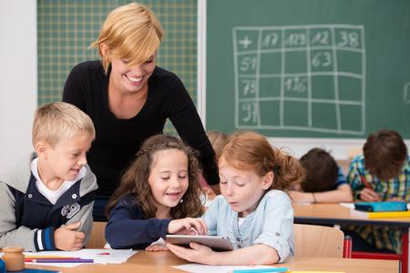 笑顔の女性先生によって見た画面上の情報で畏敬の念 exclaiming クラスでタブレットを使用して 3 つの幸せな若い学生