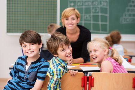 escuela primaria: Tres niños riendo felices de la escuela que dan vuelta en sus sillas durante la clase que se ríen de la cámara vigilado por una profesora joven y sonriente