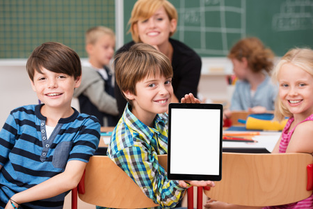 Little boy presenting a blank tablet in class turning in his chair to show it to the camera watched by smiling classmates