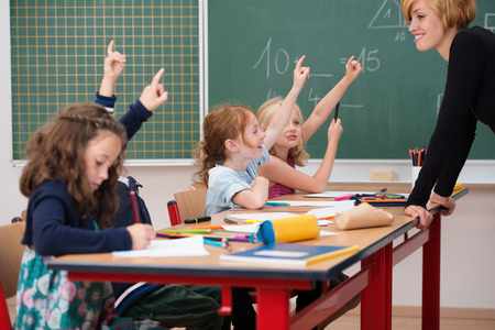 Intelligent class of young boys and girls all raising their hands to show they know the answer to a question asked by a smiling attractive young female teacher