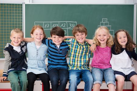 arms around: Group of happy laughing children in school sitting in a long row in front of the blackboard with their arms around each others shoulders Stock Photo