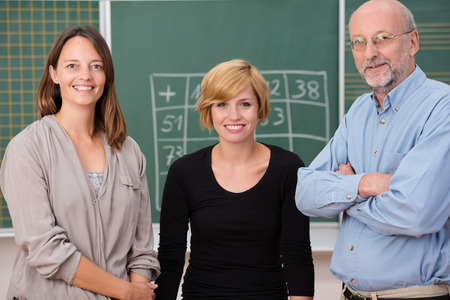 adult class: Group of three school teachers with confident friendly smiles standing in front of a class blackboard, one man and two women Stock Photo