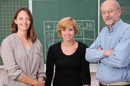 school teachers: Grupo de tres profesores de la escuela con sonrisas confiadas de pie delante de una pizarra de clase, un hombre y dos mujeres Foto de archivo