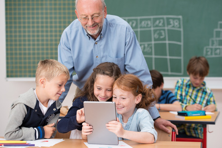 Cute happy young children in class at school smiling happily as they read something on a tablet computer under the watchful eye of a male teacher photo