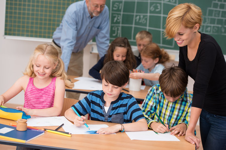 Two teachers in class with their young students with a beautiful young woman helping two small boys and a girl at a desk in the front with a male teacher working with another group behind Stock Photo