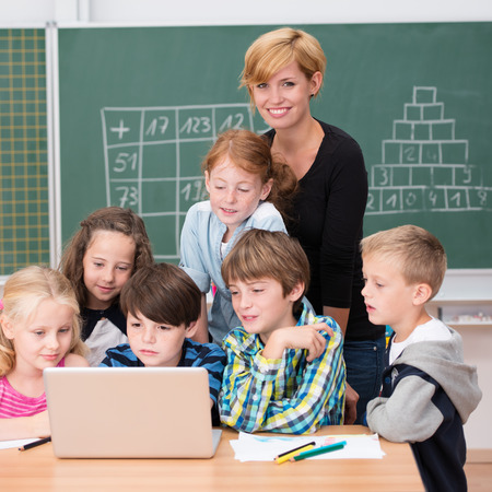 kids laptop: Group of young students in class working on a laptop with an attractive female teacher who is looking at the camera with a lovely warm friendly smile Stock Photo