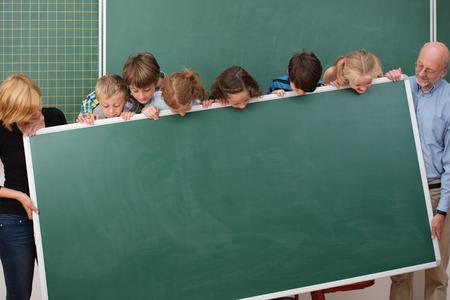 Junge Schüler und ihre zwei Lehrerinnen stehen, die eine leere Tafel alle Peering über die Oberseite zu sehen, was dort geschrieben werden Standard-Bild