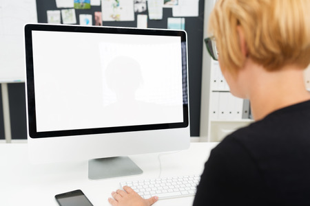 Over the shoulder view of a businesswoman working at a blank computer monitor with a white screen and copyspace