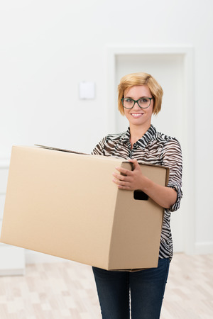 Pretty woman in glasses carrying a cardboard box in her arms as she moves house pausing to looking at the camera with a friendly smile photo