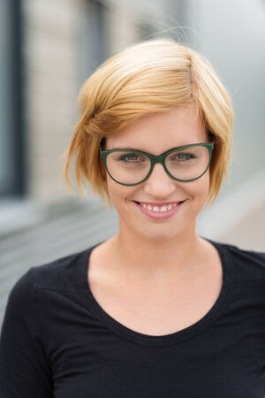 Smiling attractive young blond woman in glasses and a casual black t-shirt, head and shoulders portrait photo