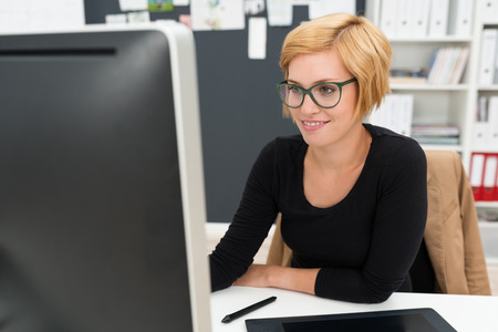 Attractive businesswoman in glasses working in the office sitting at her desk in front of the computer monitor photo
